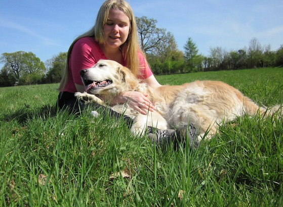 Kirsty sitting with her dog on grass